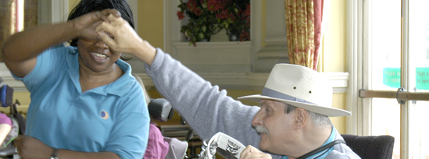 Staff member and a patient in a wheelcahir dancing at a music making session