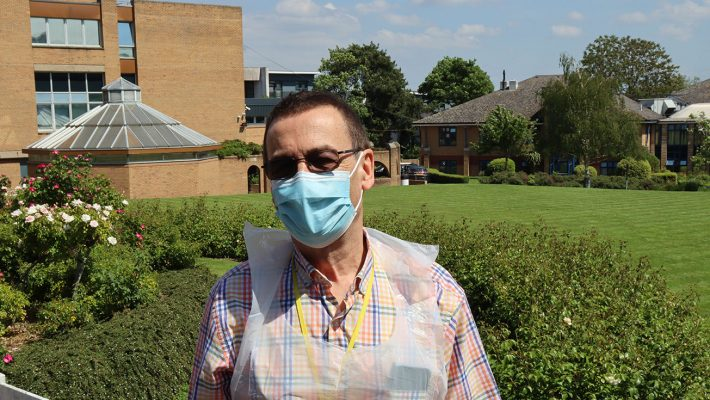 volunteer in a mask and plastic apron standing in the grounds of the RHN